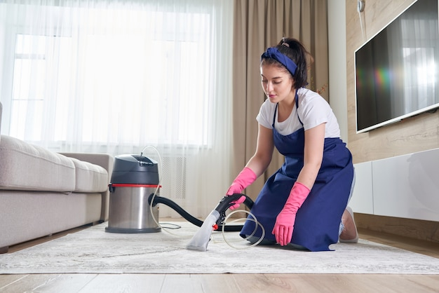 Kobieta czyszczenia dywanu w salonie za pomocą odkurzacza w domu. koncepcja usługi czyszczenia