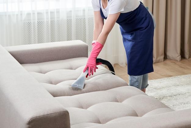 Kobieta czyszczenia kanapy z odkurzaczem w domu. koncepcja usługi czyszczenia