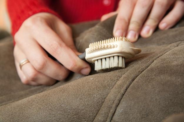 Kobieta czyszczenia skóry owczej z miotłą whisk