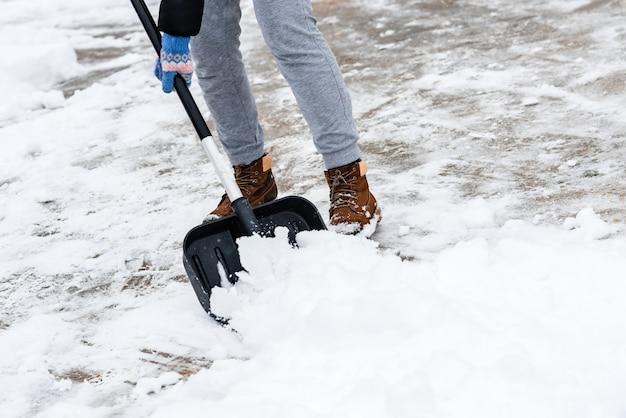 Kobieta czyszczenia śniegu z chodnika i za pomocą łopaty do śniegu.