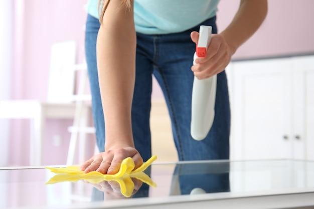 Kobieta czyszczenia stołu w pokoju