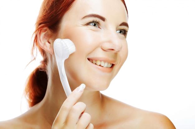 Kobieta czyszczenia twarzy pędzlem do obierania