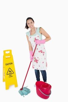 Kobieta czyszczenia w pobliżu znaku ostrzegawczego