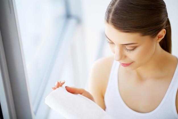 Kobieta czyszczenie skóry twarzy z białym ręcznikiem