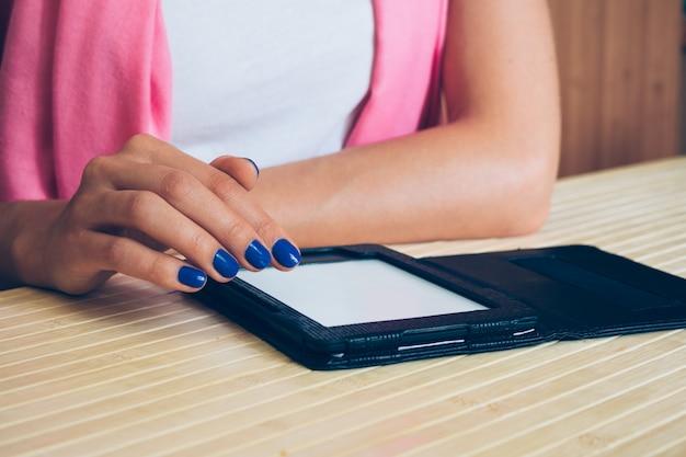 Kobieta czyta ebook przy drewnianym stołem w białej koszulce z różowym szalikiem i błękitnym manicure'em