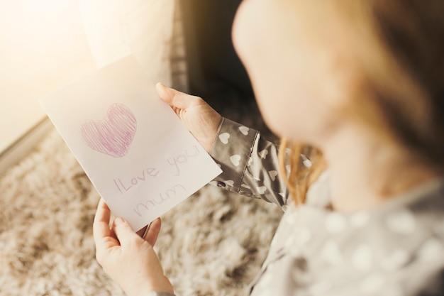 Kobieta czyta kartkę z życzeniami z kocham cię mama napis