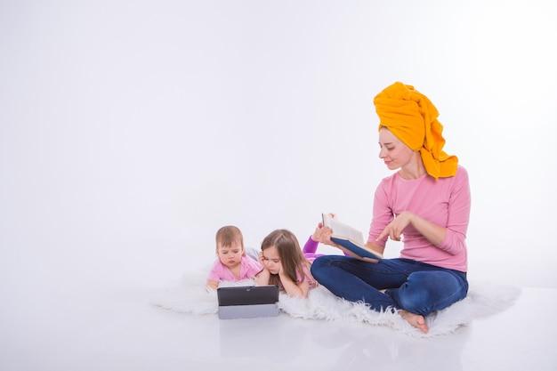 Kobieta czyta książkę, dzieci oglądają kreskówkę na tablecie. mama umyła włosy. ręcznik na głowie. hobby i rekreacja z gadżetami. rodzinne wakacje, wspólne spędzanie czasu. nauka w domu.