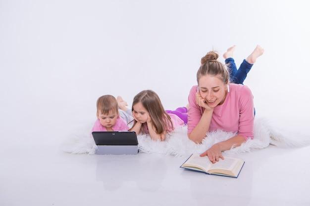 Kobieta czyta książkę, dzieci oglądają kreskówkę na tablecie.