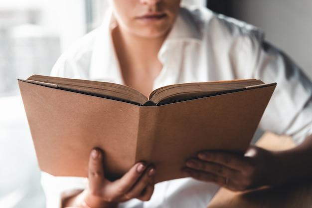 Kobieta czyta książkę. edukacja, szkolenie, nauka, hobby. manicure