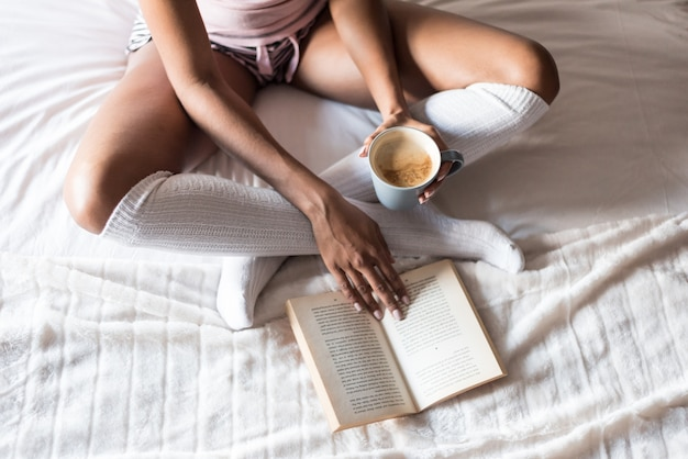 Kobieta czyta książkę i pije kawę na łóżku z skarpetami