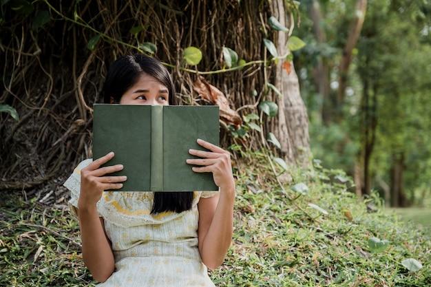 Kobieta czyta książkę i zakrywa jej twarz w parku.