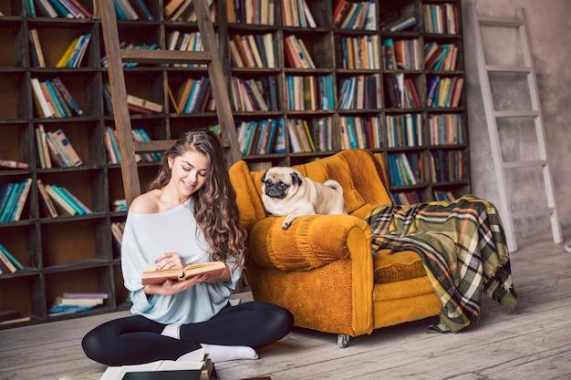 Kobieta czyta książkę na podłodze w bibliotece