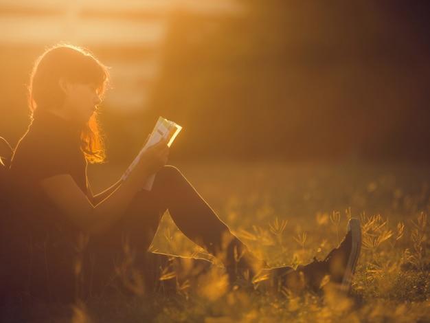 Kobieta czyta książkę na zewnątrz. jest na uniwersytecie
