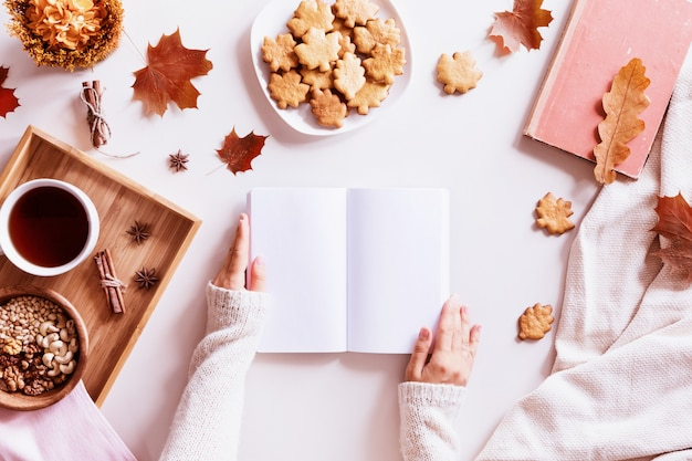Kobieta czyta książkę nad stołem z filiżanką kawy, ciastkami i jesiennymi liśćmi. widok z góry