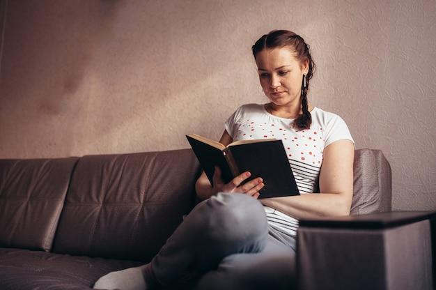 Kobieta czyta książkę podczas gdy siedzący na kanapie w domu