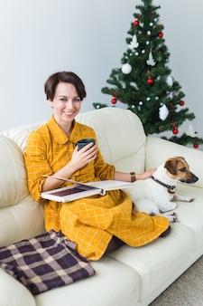 Kobieta czyta książkę przed choinką z psem jack russell terrier. boże narodzenie, święta i