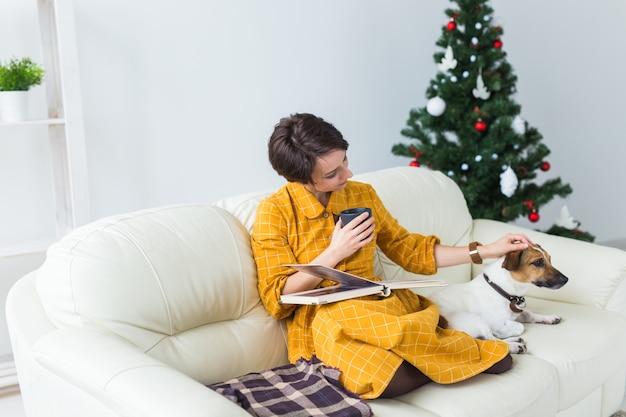 Kobieta czyta książkę przed choinką z psem jack russell terrier
