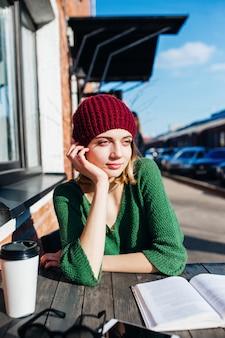Kobieta czyta książkę przy kawiarnia tarasem