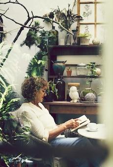 Kobieta czyta książkę przy kawiarnią