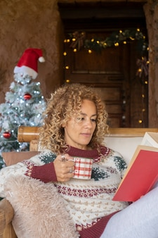 Kobieta czyta książkę z dekoracjami świątecznymi w tle