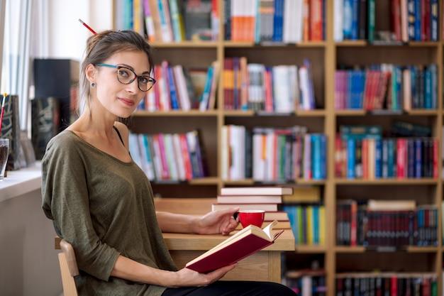 Kobieta czyta książkę z filiżanką kawy w szkłach