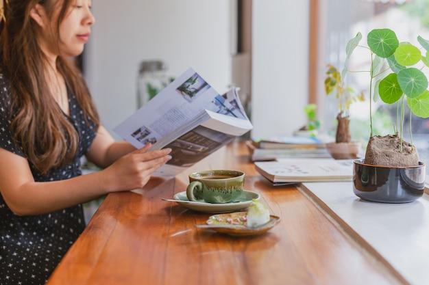 Kobieta czyta magazyn i pić kawę w kawiarni.