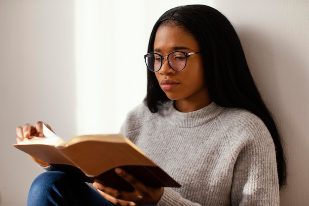 Kobieta czytająca biblię w pomieszczeniu