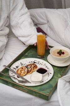 Kobieta czytająca książkę jedząc śniadanie w łóżku. kobieta w szlafroku, mając śniadanie w łóżku hotelowym, zbliżenie