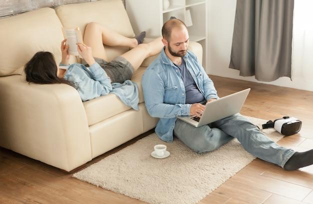 Kobieta czytająca książkę leżącą na kanapie w salonie