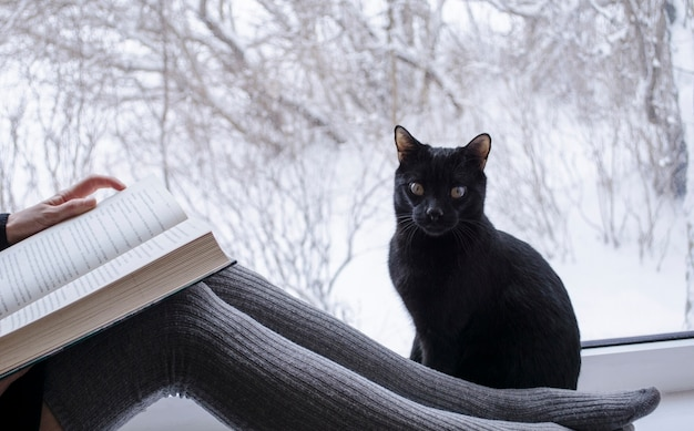 Kobieta czytająca książkę obok czarnego kota