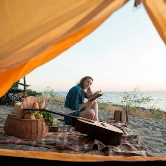 Kobieta czytająca książkę przed namiotem