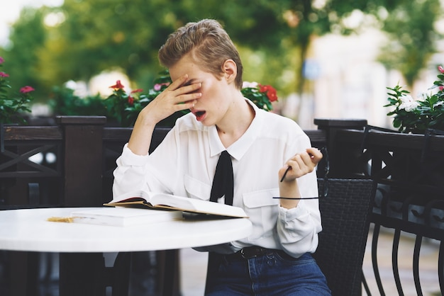 Kobieta czytająca książkę przy stole w restauracji edukacja emocje okulary kwiaty w tle
