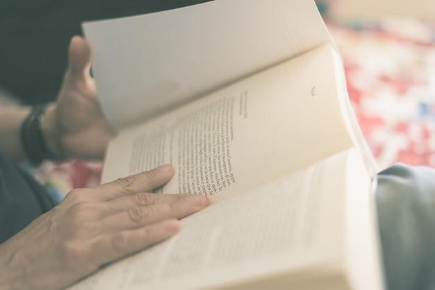 Kobieta czytająca książkę. selektywne ustawianie ostrości, zbliżenie. krzyż przetwarzany z efektem filmu w stylu vintage. ciepłe stonowane.