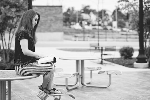 Kobieta czytająca książkę w parku