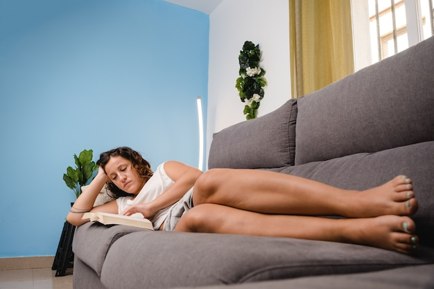 Kobieta czytająca książkę w salonie siedząc na kanapie