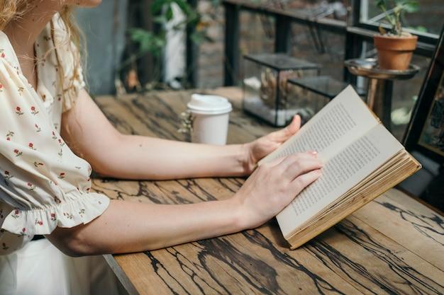 Kobieta czytająca powieść w kawiarni