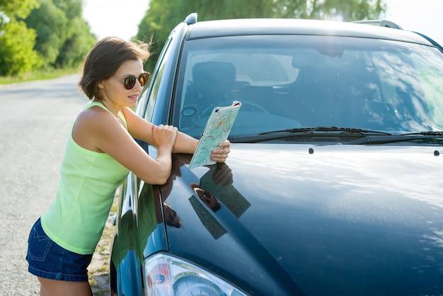 Kobieta czytanie mapy kierowcy w pobliżu samochodu