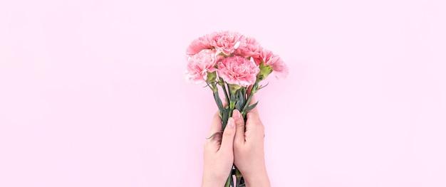 Kobieta daje bukiet goździków na białym tle na jasnym różowym tle