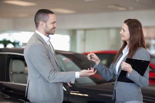 Kobieta daje kluczyki do samochodu klientowi