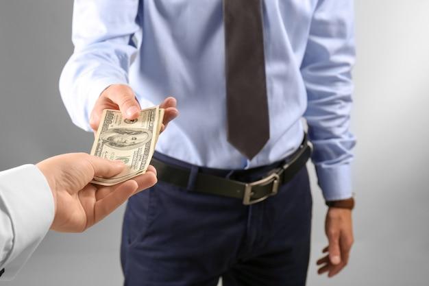 Kobieta daje pieniądze mężczyźnie na jasnej ścianie