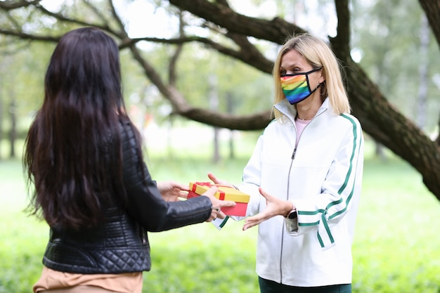 Kobieta daje prezent przyjacielowi w masce w kolorach lgbt w parku relacji tej samej płci między dziewczynami