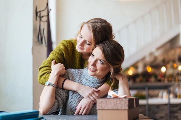 Kobieta daje prezent pudełko do swojej dziewczyny w kawiarni