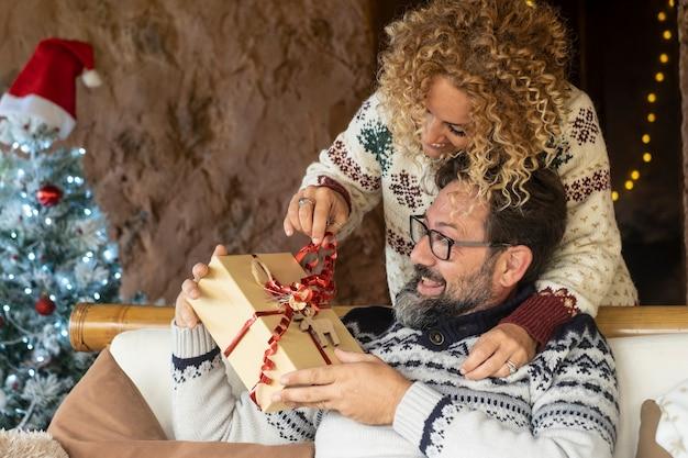 Kobieta daje prezent świąteczny mężowi w domu ciesząc się świętami