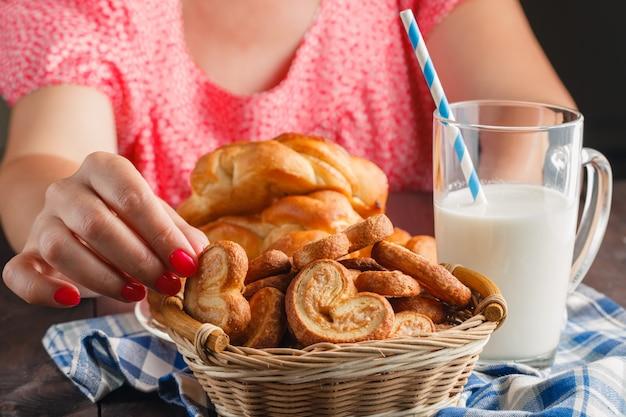 Kobieta daje produkty piekarnicze i szklankę mleka na drewnianym stole