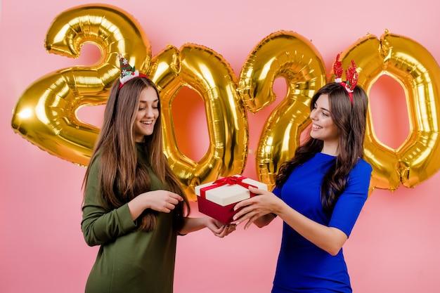 Kobieta daje pudełko jak prezent jej przyjaciółce przed złotymi balonami 2020 odizolowywającymi nad menchiami