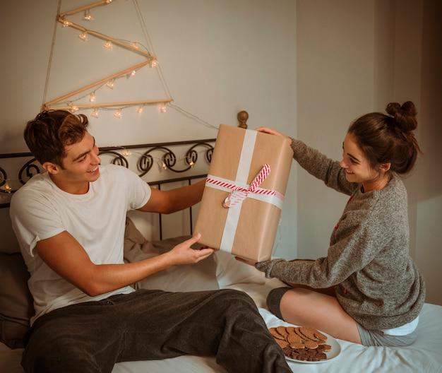 Kobieta daje pudełko mężczyźnie