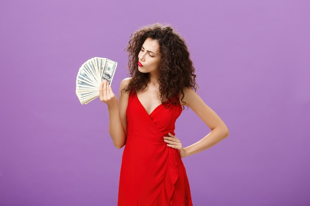 Kobieta decydująca, jak wydać dużo gotówki na trzymanie i patrzenie na pieniądze, składając usta, podejmując decyzję lub...