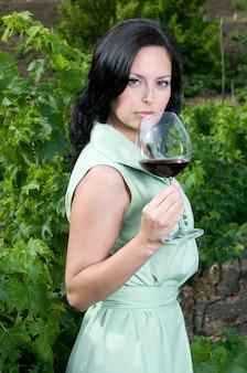 Kobieta degustująca wino ze swoich piwnic w winnicy