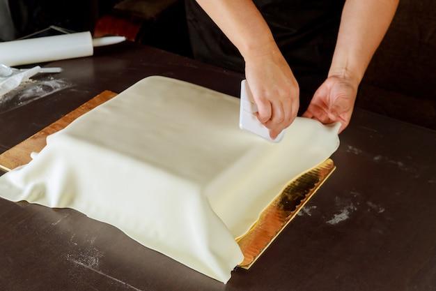 Kobieta dekorowanie kwadratowego ciasta z białą fondantem, co tort weselny