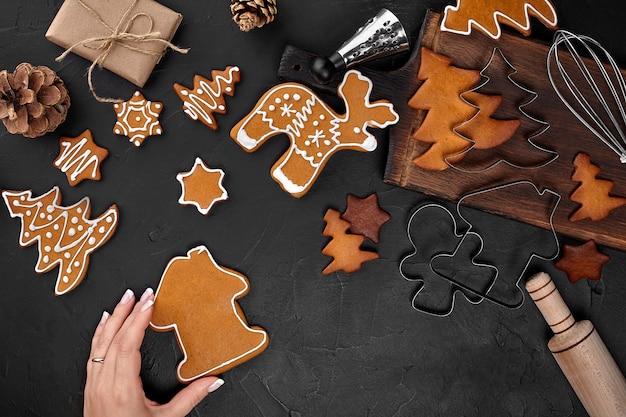 Kobieta dekorowanie pierniki świąteczne ciasteczka z cukrem pudrem na ciemnym tle. koncepcja wakacje, uroczystości i gotowania. koncepcja przygotowań do bożego narodzenia. widok z góry z miejsca na kopię.